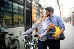 美好的夫妇走的狗和自行车户外在城市 免版税库存图片
