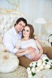 美好的夫妇,怀孕的少妇和人,拥抱爱恋坐床,在家内部 图库摄影