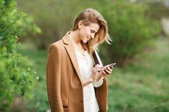 美好的女孩文字消息jn她的电话在开花庭院里在一个春日 免版税库存照片