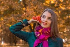 美好的女孩立场在公园在他的手上看起来去并且拿着花揪小树枝  免版税库存照片