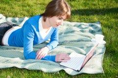 美好的女孩膝上型计算机公园工作 免版税库存照片