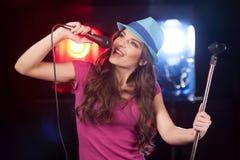美好的女孩藏品立场和身分在酒吧 免版税库存图片