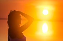 美好的女性式样享用的日落在海边 盐湖埃尔顿镇静水反射妇女` s剪影 太阳在hori后去 免版税库存图片