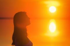 美好的女性式样享用的日落在海边 盐湖埃尔顿镇静水反射妇女` s剪影 太阳在hori后去 库存照片