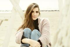 美好的女性模型微笑的坐在秋天的海滩 库存照片