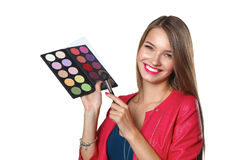 年轻美好的妇女举行在一只手和一个调色板上有油漆的和阴影构成的,中间人刷子构成的 库存照片
