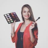 年轻美好的妇女举行在一只手和一个调色板上有油漆的和阴影构成的,中间人刷子构成的 免版税库存图片