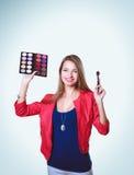 年轻美好的妇女举行在一只手和一个调色板上有油漆的和阴影构成的,中间人刷子构成的 库存图片