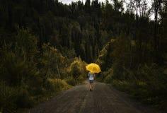 美好的妇女举行黄色伞和步行在一条乡下公路在雨下 库存图片