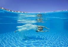 美好的妇女女孩白色礼服水下的潜水游泳蓝色晴天水池 库存照片