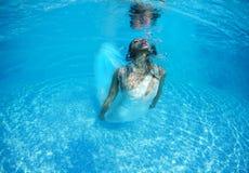 美好的妇女女孩白色礼服水下的潜水游泳蓝色晴天水池 库存图片
