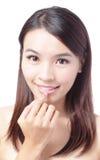 美好的妇女微笑表面接触她的嘴唇 免版税图库摄影
