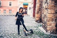 美好的妇女文字正文消息,当乘坐电滑行车在都市街道时 免版税库存图片