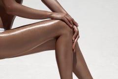 美好的妇女棕褐色腿 对白色墙壁 免版税库存照片