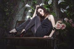 美好的妇女模型在时髦的礼服长袍的夜庭院里 免版税库存照片