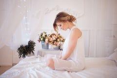 美好的妇女模型画象与新每日构成和浪漫波浪发型的 在卧室坐床 免版税库存照片