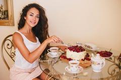 年轻美好的妇女裁减在厨房结块 免版税库存照片