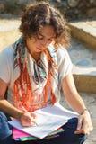 年轻美好的妇女读书和文字在外面练习本 库存图片