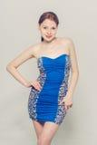 美好的妇女年轻灰色背景蓝色礼服 免版税库存照片