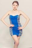 美好的妇女年轻灰色背景蓝色礼服 库存照片