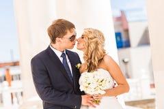 美好的婚礼夫妇在城市 他们亲吻并且互相拥抱 免版税库存照片