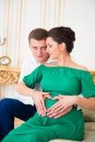 美好的对预期孩子的父母 在怀孕的肚子的心脏 库存照片
