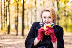 美好的少妇举行每得到的茶和尝试温暖在秋天公园 库存照片
