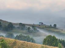 美好的山风景与和老房子、树和干草堆在一个有雾的早晨 库存图片