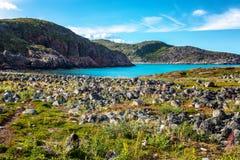美好的山风景,石头,绿草,蓝色海,天空 库存照片