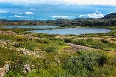 美好的山风景,石头,绿草,蓝色海,天空 免版税库存照片