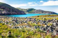 美好的山风景,石头,绿草,蓝色海,天空 图库摄影