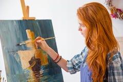 美好的平静的年轻女性画家绘画图片在艺术车间 免版税库存图片
