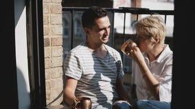 美好的年轻不同种族的夫妇喝咖啡在有古铜色金属杯子、谈话和微笑的小晴朗的阳台 影视素材