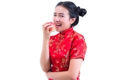 美好的年轻亚洲女服汉语画象穿戴传统cheongsam或qipao 吃红色苹果, 免版税图库摄影