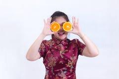 美好的年轻亚洲女服汉语画象穿戴传统cheongsam或qipao 拿着她的眼睛橙色切片前面  免版税图库摄影