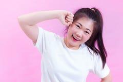 美好的年轻亚洲妇女黑发穿戴画象在桃红色背景的一件白色T恤杉 逗人喜爱的可爱的女孩 免版税库存图片