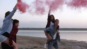 美好的年轻加上烟幕弹在手上在海滩 朋友-男人和妇女使用与彩色烟幕 股票视频