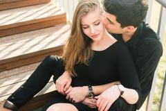美好的年轻多种族夫妇,在爱的学生夫妇,在城市坐木楼梯 美好的土耳其深色的人拥抱a 库存图片