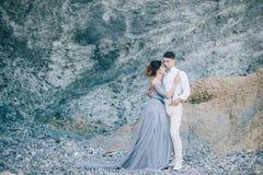 美好的年轻夫妇在他们的由海的婚礼之日在岩石附近 幸福,生活方式,家庭 免版税库存照片