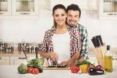 美好的年轻夫妇在厨房里,当烹调时 查看照相机 免版税图库摄影