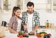 美好的年轻夫妇在厨房里,当烹调时 库存照片