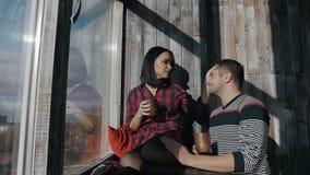 美好的年轻夫妇在家在窗口附近坐晴朗的冬日和饮料热巧克力 圣诞节 股票视频
