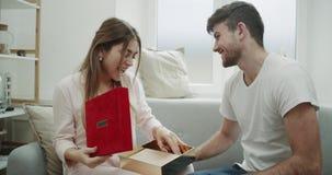 美好的年轻夫妇在庆祝华伦泰s天,人的早晨给他的夫人带来她是非常的礼物盒 股票录像