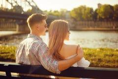 美好的年轻夫妇坐一条长凳在公园在河附近 在一条长凳的浪漫夫妇由河有约会 微笑 库存照片
