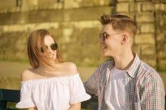 美好的年轻夫妇坐一条长凳在公园在河附近 在一条长凳的浪漫夫妇由河有约会 微笑 免版税库存照片