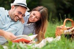 美好的年轻夫妇有一顿松弛浪漫野餐在公园 免版税库存图片