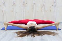 美好的年轻女人实践瑜伽asana Samakonasana平角姿势 图库摄影