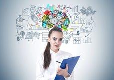 美好的年轻女实业家文字,嵌齿轮脑子 免版税图库摄影