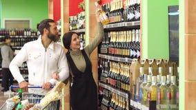 美好的年轻微笑的夫妇,当选择香槟在超级市场时 股票录像