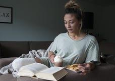 美好的年轻混合的族种、亚裔白种人、妇女阅读书在家在长沙发用热巧克力牛奶和曲奇饼特写镜头  免版税库存照片